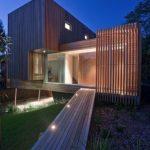 Fachada de casa de madera con pérgola vertical