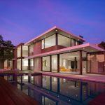 Fachada de casa vidriada con piscina