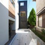Fachada de casa angosta con 3 plantas